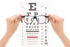 Hands holding glasses in front of an eye chart. Isolated on white background Royalty Free Stock Image