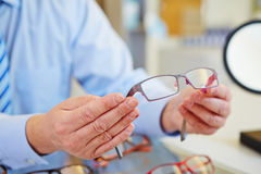 Hands holding glasses at optician stock photo