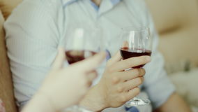 Hands holding glasses of wine. Close up of hands holding glasses with red wine indoors stock footage