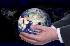 Hands holding the globe. With a mainly dark background of cities viewed from space Stock Image