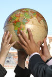 Hands holding the globe. Representing teamwork Royalty Free Stock Images