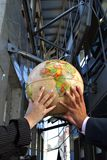 Hands holding the globe. Between buildings Stock Images