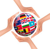 Hands holding globe with flags of world Royalty Free Stock Photos