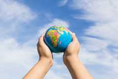 Hands holding globe with sky background Royalty Free Stock Photos