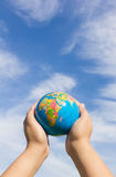 Hands holding globe with sky background Royalty Free Stock Photography