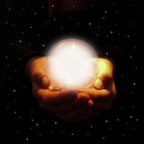 Hands holding glowing crystal ball. Hands holding bright glowing crystal ball appearing out of starry night sky Stock Photo