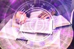 Hands holding glowing zodiac wheel book. Close up of hands holding glowing book with zodiac wheel. Magic and astrology concept. Double exposure royalty free stock photos