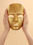 Hands holding gold mask Royalty Free Stock Photography