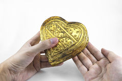 Hands holding golden heart Stock Images