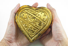 Hands holding golden heart Stock Photo