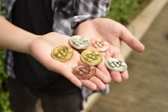Bitcoin in the hands. Hands Holding Golden and Silver Bitcoin Virtual Money Cryptocurrency. Bitcoin in the hands of a boy holds a metal coin of crypto currency royalty free stock images