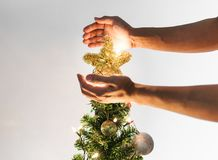 Hands holding golden star on Christmas tree with bright lights, Christmas holiday concept. S Stock Image