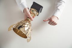 Hands holding golden trophy on white desk. Business, Success stock image