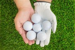 Hands holding 6 golf balls