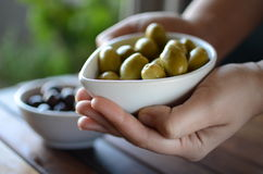 Hands holding green and black olives in ceramic pots. On a wooden table Stock Photo
