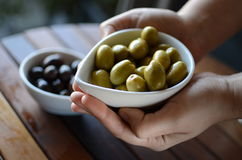Hands holding green and black olives in ceramic pots. On a wooden table Stock Image