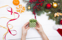 Hands holding green gift box on Christmas decorations background Royalty Free Stock Images
