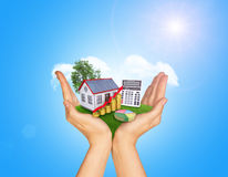 Hands holding green grass with house on ground Royalty Free Stock Photography
