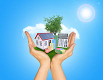Hands holding green grass with house on ground Royalty Free Stock Photo