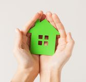 Hands holding green house. Closeup picture of woman hands holding green house Royalty Free Stock Photos