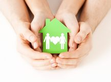 Hands holding green house with family. Real estate and family home concept - closeup picture of male and female hands holding green paper house with family Stock Photography