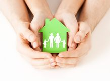 Hands holding green house with family. Real estate and family home concept - closeup picture of male and female hands holding green paper house with family Stock Images