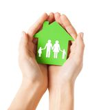Hands holding green house with family. Real estate and family home concept - closeup picture of female hands holding green paper house with family Royalty Free Stock Photography