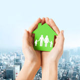 Hands holding green house with family Stock Images