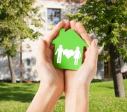 Hands holding green house with family. Real estate and family home concept - closeup picture of female hands holding green paper house with family stock image