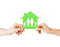 Hands holding green house with family. Real estate and family home concept - isolated picture of male and female hands holding green paper house with family Stock Image