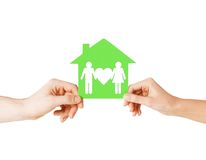 Hands holding green house with family Royalty Free Stock Images