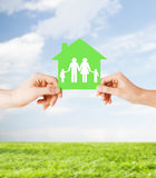 Hands holding green house with family. Real estate and family home concept - isolated picture of male and female hands holding green paper house with family Stock Photos