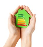 Hands holding green paper house. Energy saving, real estate and family home concept - closeup of female hands holding green paper house with energy efficiency Stock Photography