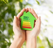 Hands holding green paper house. Energy saving, real estate and family home concept - closeup of female hands holding green paper house with energy efficiency Royalty Free Stock Images