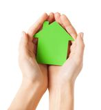Hands holding green paper house. Real estate and family home concept - closeup picture of female hands holding green blank paper house Royalty Free Stock Photography