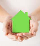 Hands holding green paper house. Real estate and family home concept - closeup picture of female hands holding green blank paper house Stock Photography