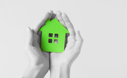 Hands holding green paper house stock photos