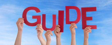 Hands Holding Guide in the Sky. Many Hands Holding the Word Guide in the Sky Royalty Free Stock Photography