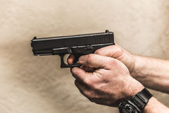 Hands Holding Gun with Finger on Trigger Royalty Free Stock Photography