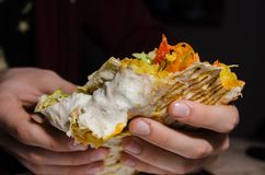 Hand holding shawarma on white plate stock photography