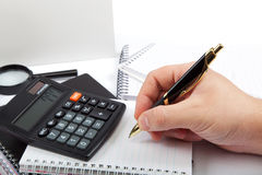 Hand with pen and calculator near documents. Royalty Free Stock Image