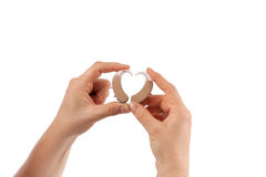Hands holding hearing aids and forming heart shape Royalty Free Stock Photography