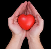 Hands holding heart. Hands holding red heart over black background Royalty Free Stock Photography