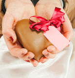 Hands holding a heart shaped chocolate Royalty Free Stock Images