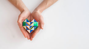 Hands holding a heart. Hands taking care of heart twist toy royalty free stock photos