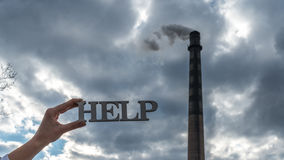 Hands holding help text next to chimney polluting the air Stock Photo