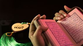 The Holy book of muslims/ Quran hands hold the koran. Hands Holding holy book of muslims on the black background royalty free stock photography
