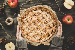 Hands holding homemade delicious apple pie on the wooden table. Top view stock photo