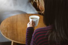 Hands holding hot cup of coffee or tea in morning royalty free stock photos