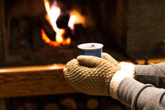 Hands holding hot drink by the fireplace Royalty Free Stock Images